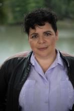 A heavy set adrogynous person with short, dark, curly hair, brown eyes and olive skin wears a lavander guayabera under a black leather jacket and stands in front of the lagoon at New Orleans' City Park.